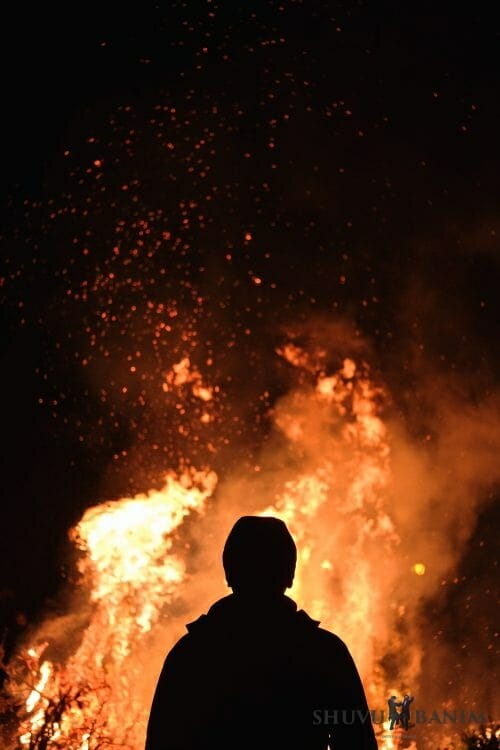 A silhoutted man stands in front of a raging bonfire