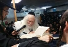 Rabbi Berland on the dais at the Beit HaRav