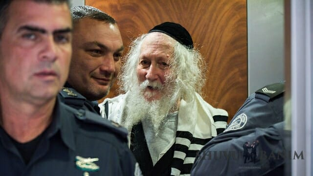 Rabbi Berland surrounded by police in court